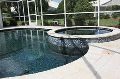Completed pool and deck renovation.  Tumbled edge travertine coping and travertine deck.  New Great American Waterfall Company aqua spout spillways, Luv Tile Luv-Mix mosaic tile and Pebble Tec Midnight Blue interior finish.