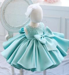Cute Turquoise Blue Big Bow Dress--Made To Order - High Quality Round Neckline Sleeveless Knee Length Pearl & Crystal Applique Little Girl Ruffle Dress With Big Bow Front. Perfect dress for baptism, communion, wedding, birthday party or any special occasion. Available from 9 months -12 years. Material: Cotton, satin. Colors: White, Pink & Turquoise. Please do compare your little girl's measurements with our size chart.