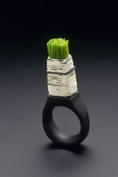 This was made in 2004 entirely out of Fimo. Cynthia carved away the darker layer to reveal the white clay below. She also embedded her micromosaic threads into soft clay. It was first published in the Lark Books 1000 Rings book.