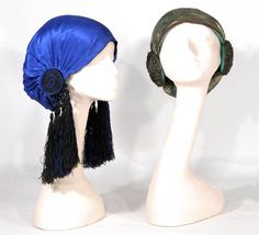 Two Woman's Draped Silk Orientalist Caps French, circa 1907  Stylized turban design, the first black lined in royal blue gathered to modified orielletes of medallions exuding black and blue silk tassels; the second of metallic gold gauze lined in jade green silk gathered to each side with braided metallic gold medallions embroidered with faux emeralds.