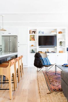 Boho-chic open-plan living space with built-in bookshelves, layered rugs, and a kitchen island with wood barstools and metalic pendant lights