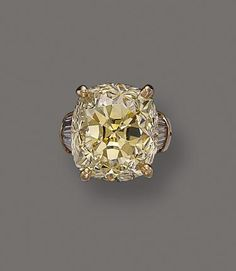 The cushion-shaped diamond of light yellow color weighing approximately 37.00 carats, flanked by 10 tapered baguette diamonds weighing approximately 1.00 carat, within a raised, openwork 18 karat gold mounting.