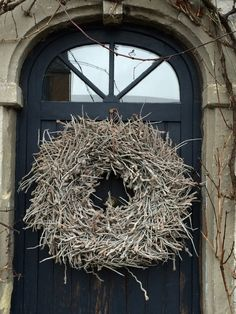 fabulous stick wreath...looks perfect on that door and in that imposing doorway..