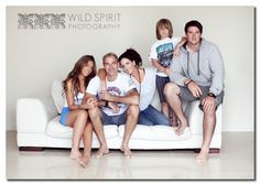 Unique pose of a family on a couch.
