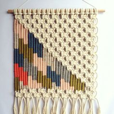Woven macrame wall hanging made from woollen and bamboo yarns and cotton rope. Approx. 62 cm / 24 inches high (including fringe), and 40 cm / 16