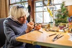 Annette Petersen, 93, works on a Wee Forest Folk piece in her Carlisle, MA studio, where the family-run enterprise specializes in crafting tiny mice as part of its line of tiny collectible mouse figurines.