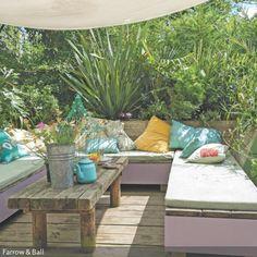 Take a seat! Auf der gepolsterten Sitzauflage mit den farbig gemusterten Sofakissen kann man super entspannen. Der Look der mediterranen Garten-Lounge entsteht vor allem durch die Kombination aus dem natürlichenen Holztisch mit passendem Bodenbelag sowie den mediterranen Pflanzen, die teilweise in Terrakottatöpfen drapiert wurden. Ein weißes Sonnensegel sorgt für den nötigen Sonnenschutz und vervollständigt die Garten-Lounge zu einem abgeschlossenen Bereich im Garten.