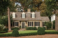 """""""We made subtle but important changes to the front exterior,"""" says Brad, """"such as painting the brick a warm light brown to help the house nestle into the surrounding trees."""" Brad also added a cedar-shingled roof, a flared awning over the front door, and charming black shutters to the upstairs dormer windows, all giving the house more architectural definition.  See more of this Cape Cod Cottage Makeover"""