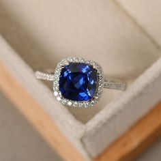 This halo ring features a 8*8mm cushion cut lab sapphire and sterling silver finished with rhodium. Customization is available. It is made by hand, and it will take about 7 days to finish the ring after your payment is completed. Any question, just let me know. :)   My shop homepage: https://www.etsy.com/shop/LuoJewelry?ref=l2-shopheader-name
