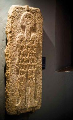 """La Estela Funeraria conocida como """"El Astronauta"""" estuvo durante muchos años en una pared exterior del cementerio del Casar. Su datación pudiera estar en torno al siglo I o II, actualmente se encuentra en la Sala nº 2 del Museo Arqueológico de Cáceres."""