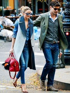 Olivia Palermo wears a denim shirt, skinny jeans, heels, a wool vest, red satchel, and mirrored sunglasses