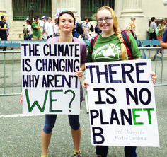 UNCA students Sarah Harrell, left, and Jane Smith, right, hold signs at the People's Climate March. Photo Illustration by Merry Hughes - Contributor