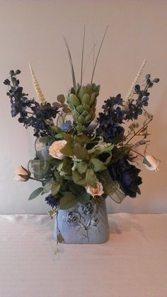 Gorgeous, high quality flowers sprung from a pretty light blue ceramic container. Very artistic piece using roses, delphinium, and other unusual flowers. Embellished with silk ribbon. Could be used in a living room, bedroom, or of your choosing.