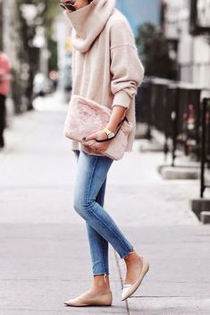 A cowl neck pastel pink oversized sweater is worn with blue jeans, tan loafers and a furry pink clutch.