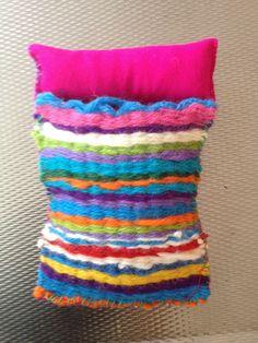 Slaapzakje voor de kabouter. De deken is geweefd op een weefraam. De onderzijde is gemaakt van vilt. Het kussentje is gevuld met schapenwol.