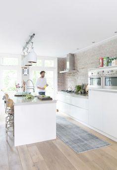 Mooie lichte keuken in Scandinavische stijl. De industriële stijl komt voornamelijk in de muur en accessoires terug.