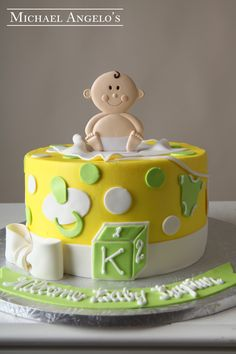Baby Topper #70Baby This cake is iced in buttercream and decorated with fondant cut-outs in the shape of baby items. Polka dots were added to bring a little extra fun. The topper is a plastic toy.