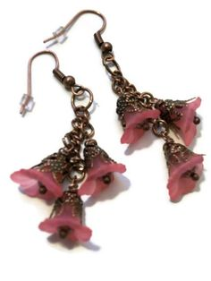 "These vintage inspired earrings are made with a Beautiful deep Pink blush Lucite trumpet bead and copper filigree bead caps. I have added small peacock crystals in the center for a little sparkle. These earrings have a 1 3/4"" drop and are hung on Copper ear wires. $25.00"