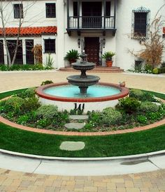 water fountain surrounded with garden bed of rocks and pebbles looks great