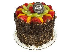 Chocolate Seasons Cake   Rich chocolate cake filled with bavarian cream and fresh sliced strawberries and bananas. Iced in Freed's signature true European chocolate buttercream, topped with assorted fruit (may vary slightly from as shown), and coated around the sides with chocolate shavings.