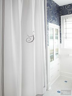 An embroidered monogram and ribbon glued on with permanent fabric glue, such as Fabri-Tac, are inexpensive ways to give a store-bought shower curtain a custom look.