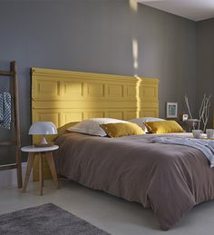 Des soubassements s'offrent une seconde vie en servant de matériau de base pour la réalisation d'une tête de lit à l'aspect brut et authentique.