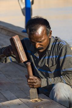 A laborer shapes timber with a hammer and chisel in a dhow ship building yard. Sur, Ash Sharqiyah Region, Gulf of Oman, Sultanate of Oman.