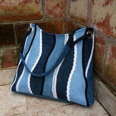 Džíska modrobíle prýmková Větší kabelka ze středně modré recydžínoviny. Přední díl je ozdobený aplikací doplňkových odstínů džínoviny a prýmky v bílé a černé barvě. Kabelka je pečlivě podlepená, dobře drží tvar, má modrou džínovou podšívku se třemi kapsami. Je uzavíratelná na pevný zip. Složené ucho z černého popruhu provlečené kovovými kroužky ...