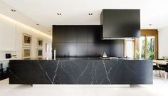 that gigantic island is amazing in the way it's floating on that thin base. monolithic cabinet, hood and island. nice!