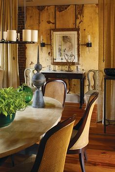 The warm color of the rustic paneling and caned chairs, the sconces and candlier, the side chairs