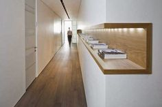 What better way to fill a long narrow hallway than with a wood lined niche and LED lighting.