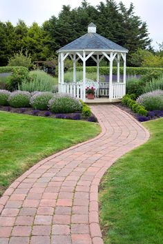 A neat, well organized garden is served well by a crisp white gazebo with simple lines. This bright building makes this space truly pop.