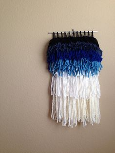 this fluffy navy blue ombré fringe wall hanging is made with a mix of black, navy, light blue and multiple shades of white cotton and acrylic yarn