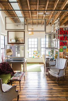 """A """"wall"""" of vintage picture frames separates one half of this open living space from the other."""