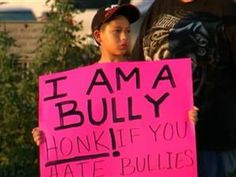 Father makes son hold sign for bullying student....heck of a parent!