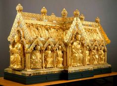 The golden Shrine of Charlemagne, made in Aachen in 1215, still houses the emperor's remains (except for the bits kept in reliquaries in the Treasury). On the front gable Charlemagne is shown enthroned between Pope Leo III and Archbishop Turpin of Reims. The long sides of the shrine depict 16 rulers who donated to the shrine. The other gable has the Virgin Mary flanked by the archangels Gabriel and Michael. Above them are the personified virtues of faith, charity and hope.