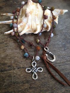Gorgeous colorful semi precious stones are crocheted onto dark brown nylon cord featuring a stunning sterling silver cross pendant. The strand