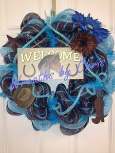 This wreath is designed as a screen door wreath. It's brown with blue striped foil mesh is accented by blue mesh, blue deco flex tubing bows, bright blue and brown flowers, a cowboy hat, a boot, and a rustic star. Topped off with a Welcome sign that leaves no doubt that horses are loved in this home!