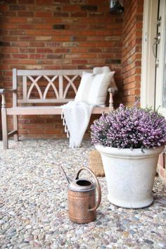 Front porch styling with pot of lavender, copper watering can and bench with throw blanket