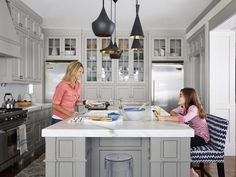 Like the airy look of a white kitchen but this one has a twist, the cabinets are painted light gray (Gray Owl by Benjamin Moore). Two-seater benches are from Lee Industries. They scoot up to a 52-inch-by-127-inch marble island.