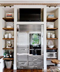 In Mary Jo Bochner's Savannah, Georgia, kitchen, a Sony TV is tucked into a niche above the refrigerator. Open shelves made with wood salvaged from the torn-down walls hold a collection of white ironstone.   - HouseBeautiful.com