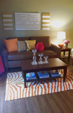 Living room part one, orange zebra rug, clear candle holders, orange and pink pillows, gold canvas