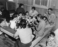 Multiple generations of Japanese Americans at meal time in the Manzanar Internment Camp barracks dining area.