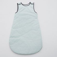 """La gigoteuse imprimée """"motif géométrique"""" en percale pur coton. Doublure contrastante en  jersey pur coton. Fermeture zippée sur le côté et pressionnée aux   épaules. Garnissage 100 % polyester."""