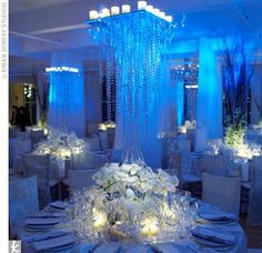 Jessika and Michael's reception area looks like a spectacular winter wonderland. Dripping icy chandeliers and lush, white centerpieces lit from below combine to create a wow-inducing scene awash in icy blue lighting.
