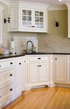 "Like the backsplash and floor. House we're going to buy has bright white tile and aggregate floor, will have to change! ""White Wednesday"" Kitchen of the Day: White cabinets with black granite and wood flooring."