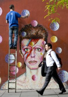 Australian street artist James Cochran, puts the finishing touches on a wall portrait of David Bowie in Brixton, South London, on June 19th,...