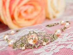 "This upcoming fall and winter, wedding trends are geared towards appreciating the past. Our ""Peach Champagne"" bracelet has wonderful displays of soft peach and antique brass that combine with delicate pearls and crystals for a romantic piece. With throwbacks to the 1950s and vintage-inspired styl..."