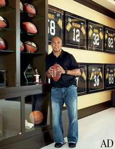 """HINES WARD """"I spent years clipping pictures from magazines,"""" explains two-time Super Bowl champion Hines Ward of the inspiration for his Atlanta home, which was designed by architect David Grace. Ward is seen here in his trophy room, which is painted in the Pittsburgh Steelers' signature black-and-gold color palette. (November 2010)"""