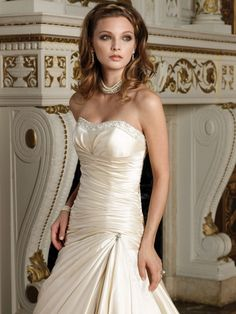 This strapless dress features complicated handcrafts work, like embroidery, beading, and drapes. It's an exquisite pattern for fall 2010. Recommended color: Champagne, White, Ivory.